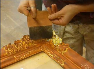 Photo showing the application of gold leaf on the corner of an ornate picture frame